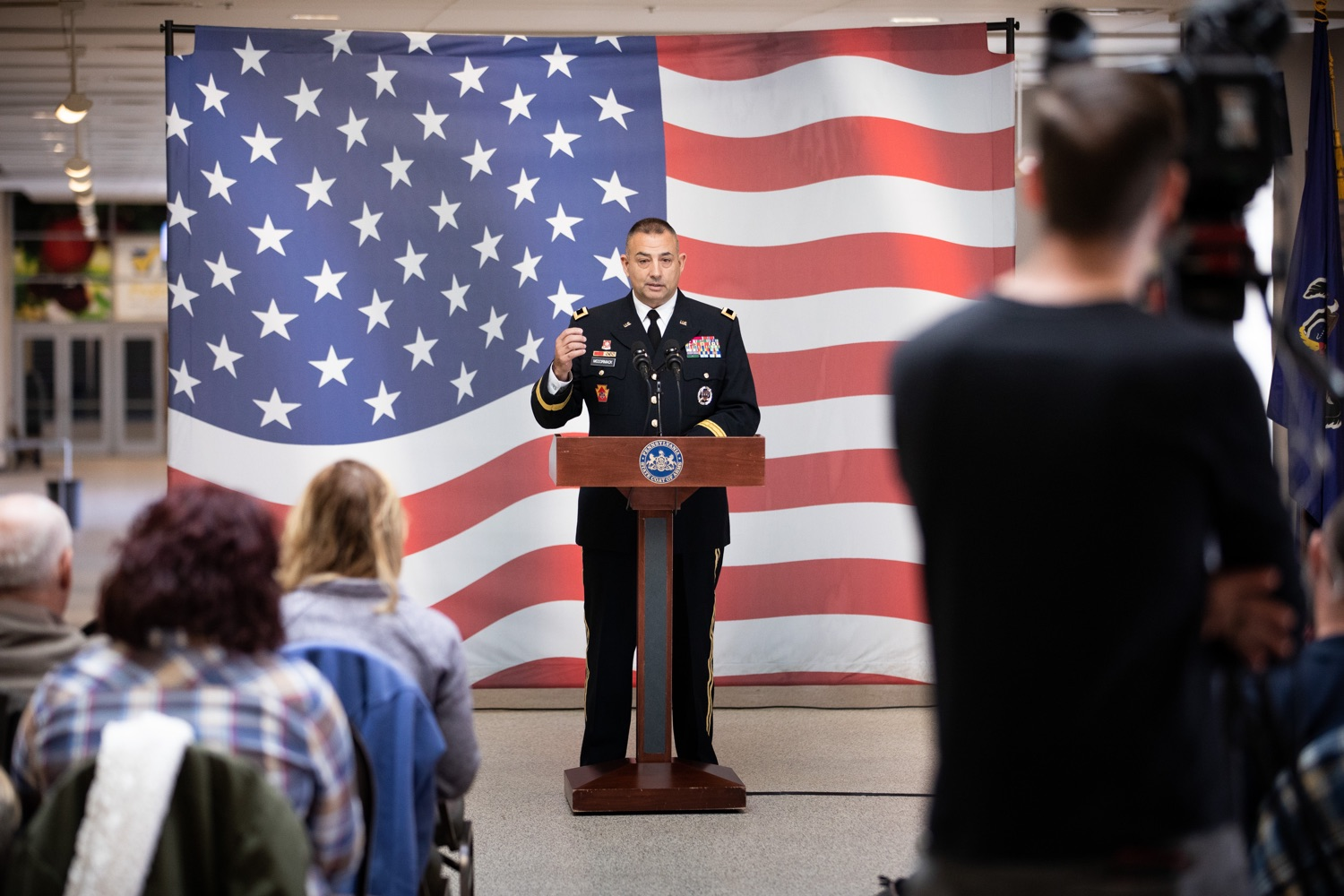 """<a href=""""https://filesource.wostreaming.net/commonwealthofpa/photo/17530_agric_homegrown_heroes_dz_022.jpg"""" target=""""_blank"""">⇣Download Photo<br></a>Veterans Affairs Brig. Gen. Mark McCormack speaks at the ceremony.  Agriculture Secretary Russell Redding and Department of Military and Veterans Affairs Brig. Gen. Mark McCormack honored members of the PA Preferred Homegrown by Heroes program for their service to our nation and to Pennsylvania, through their military service and work in agriculture. The two agencies celebrated Pennsylvanias investments in farmer-veterans in a ceremony at the Pennsylvania Farm Show Complex and Expo Center. Harrisburg, PA - Friday November, 8 2019."""