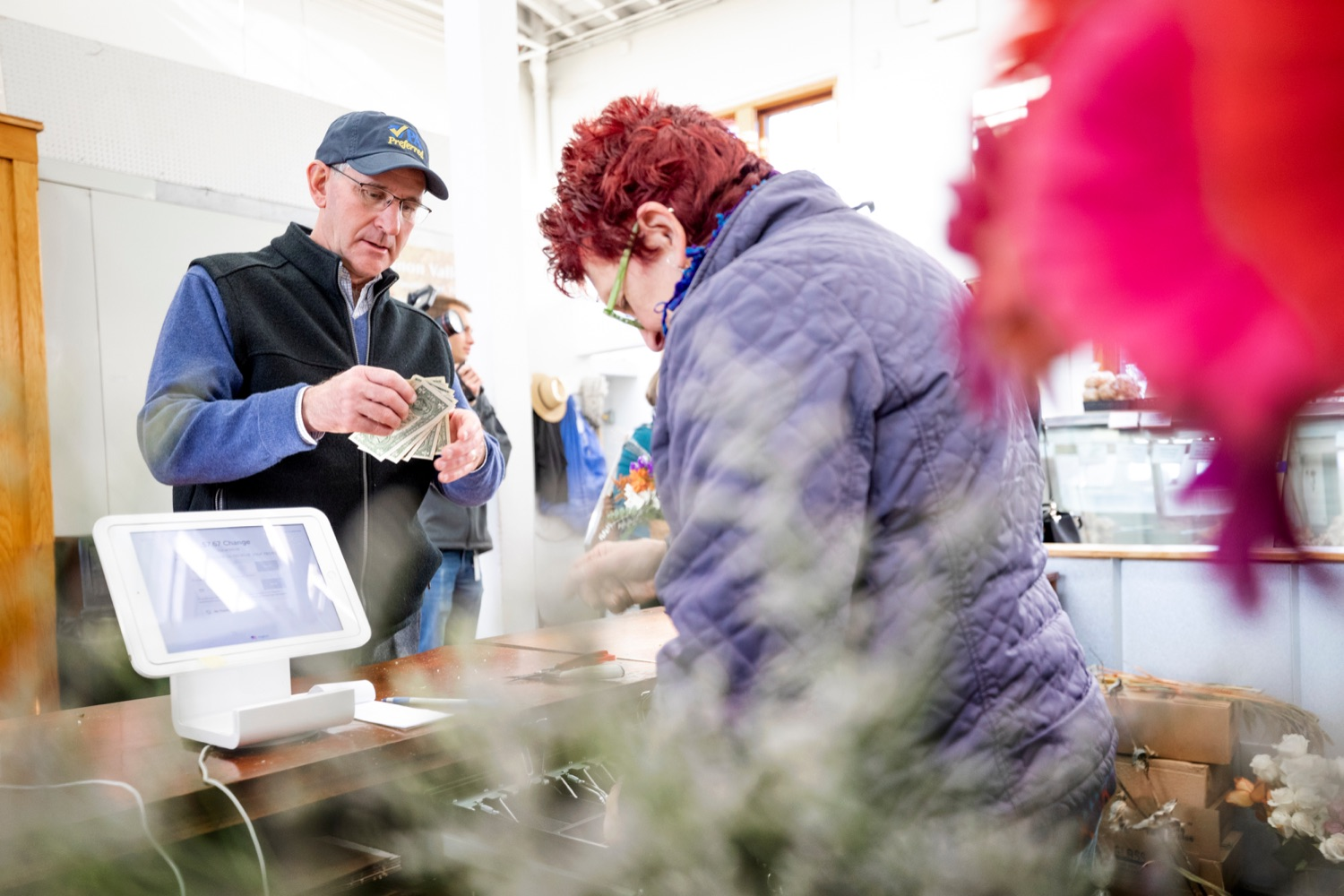 """<a href=""""https://filesource.wostreaming.net/commonwealthofpa/photo/17546_AGRIC_Buy_Local_NK_007.JPG"""" target=""""_blank"""">⇣Download Photo<br></a>Pennsylvania Department of Agriculture Secretary Russell Redding purchases flowers from Dolores McGee, owner of D. McGee Design Studio, while grocery shopping for Thanksgiving dinner inside Broad Street Market on Thursday, November 21, 2019."""
