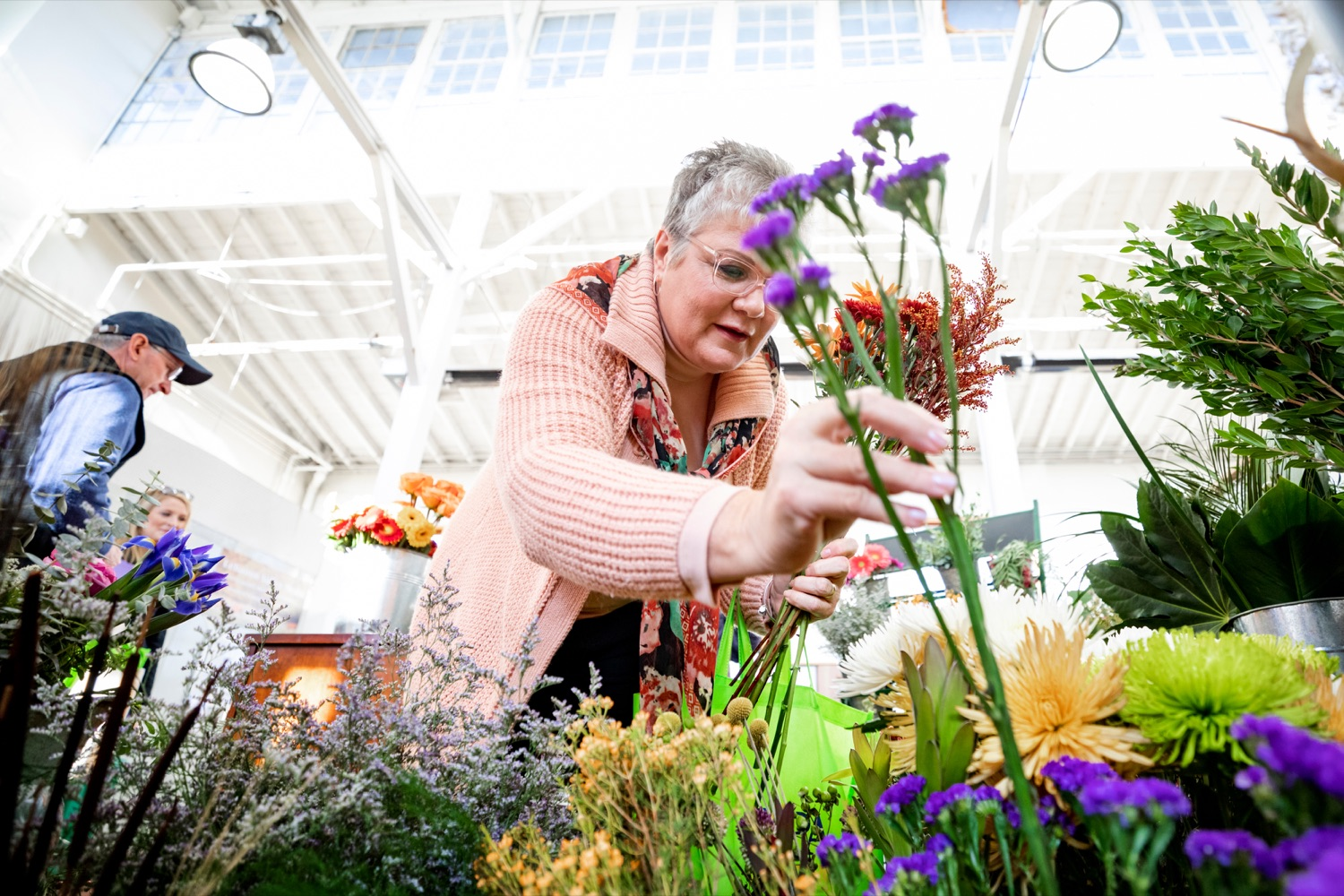 """<a href=""""https://filesource.wostreaming.net/commonwealthofpa/photo/17546_AGRIC_Buy_Local_NK_009.JPG"""" target=""""_blank"""">⇣Download Photo<br></a>Nina Redding picks out flowers from D. McGee Design Studio while grocery shopping for Thanksgiving inside Broad Street Market on Thursday, November 21, 2019."""