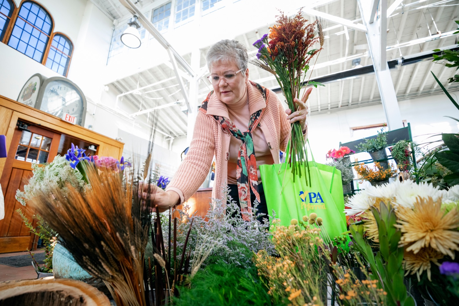 """<a href=""""https://filesource.wostreaming.net/commonwealthofpa/photo/17546_AGRIC_Buy_Local_NK_012.JPG"""" target=""""_blank"""">⇣Download Photo<br></a>Nina Redding picks out flowers from D. McGee Design Studio while grocery shopping for Thanksgiving inside Broad Street Market on Thursday, November 21, 2019."""