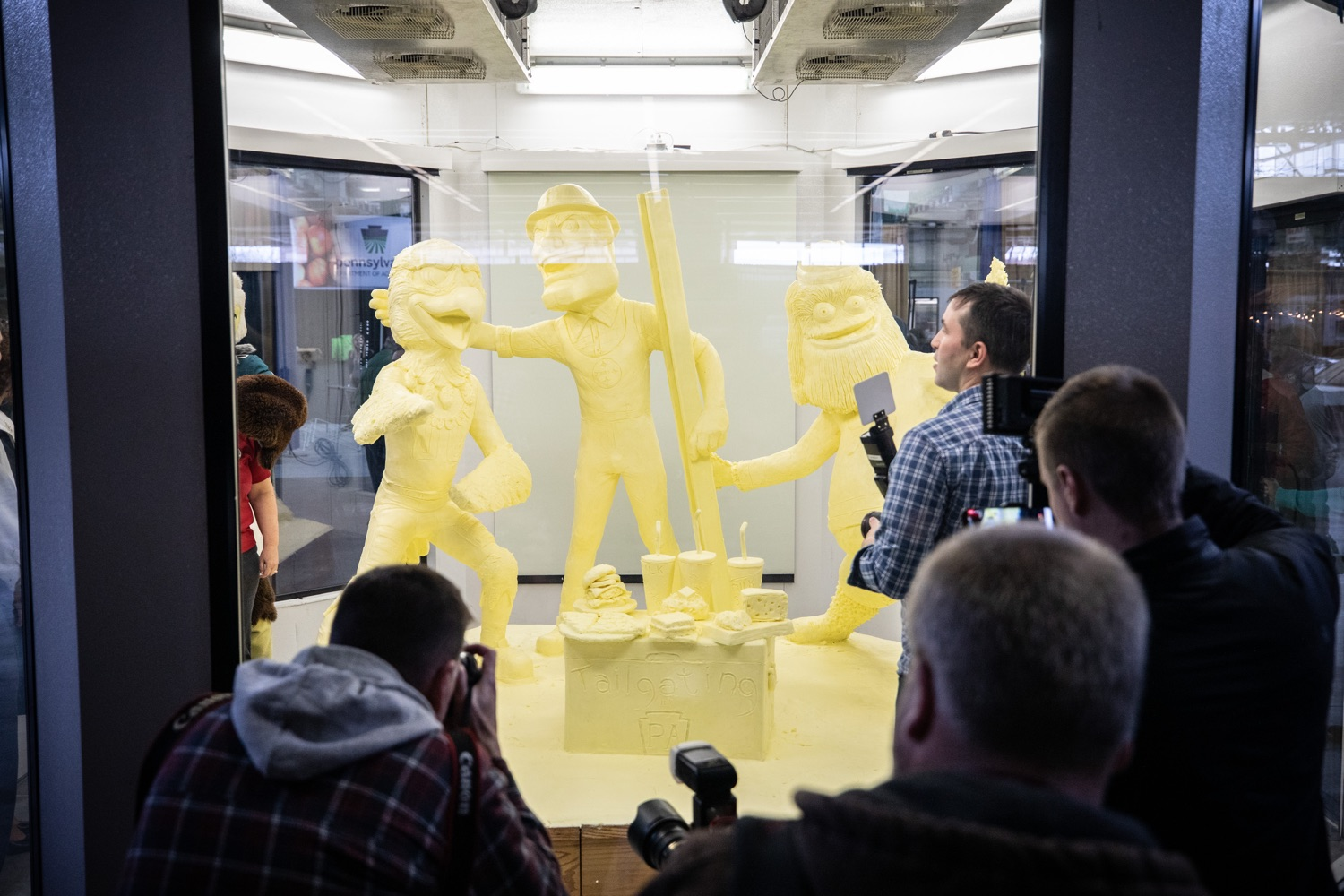 "<a href=""https://filesource.wostreaming.net/commonwealthofpa/photo/17646_agric_butter_sculpture_dz_006.jpg"" target=""_blank"">⇣ Download Photo<br></a>Press crowdind around the butter sculpture for the big reveal. Lt. Governor John Fetterman and Secretary of Agriculture Russell Redding today unveiled the 2020 Pennsylvania Farm Show butter sculpture, carved from a half-ton of butter depicting three of Pennsylvanias beloved professional sports mascots: Philadelphia Flyers Gritty, Philadelphia Eagles Swoop, and Pittsburgh Steelers Steely McBeam celebrating with a spread of Pennsylvania dairy products. The sculpture, a long-time Farm Show staple, encourages Pennsylvanians to be a fan of Pennsylvania dairy and give a cheer to the more than 6,200 dairy farmers in the commonwealth.  Harrisburg, PA  January 2, 2020"