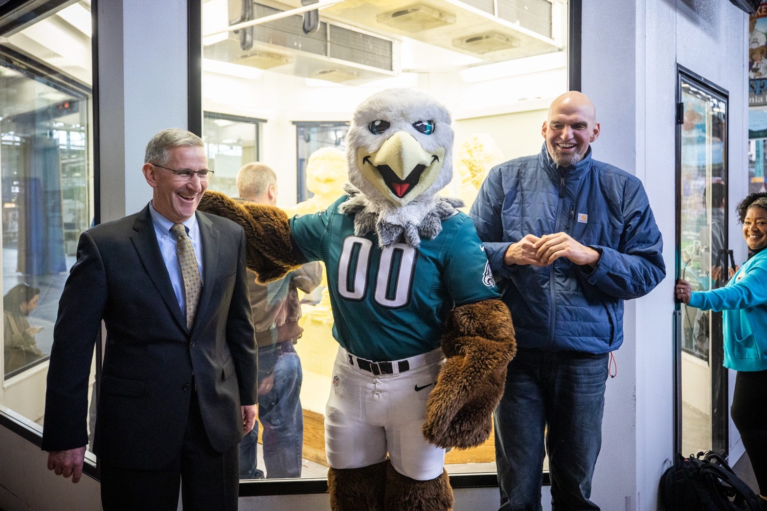 "<a href=""https://filesource.wostreaming.net/commonwealthofpa/photo/17646_agric_butter_sculpture_dz_022.jpg"" target=""_blank"">⇣ Download Photo<br></a>Philadelphia Eagles Swoop, Lt. Governor John Fetterman,  and Secretary of Agriculture Russell Redding at the Pennsylvania Farm Show butter sculpture.  Lt. Governor John Fetterman and Secretary of Agriculture Russell Redding today unveiled the 2020 Pennsylvania Farm Show butter sculpture, carved from a half-ton of butter depicting three of Pennsylvanias beloved professional sports mascots: Philadelphia Flyers Gritty, Philadelphia Eagles Swoop, and Pittsburgh Steelers Steely McBeam celebrating with a spread of Pennsylvania dairy products. The sculpture, a long-time Farm Show staple, encourages Pennsylvanians to be a fan of Pennsylvania dairy and give a cheer to the more than 6,200 dairy farmers in the commonwealth.  Harrisburg, PA  January 2, 2020"