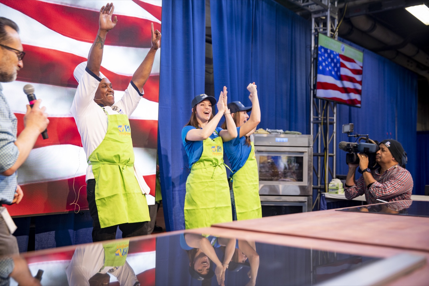 "<a href=""https://filesource.wostreaming.net/commonwealthofpa/photo/17651_AGRIC_ARMY_NAVY_COOKOFF_CZ_01.jpg"" target=""_blank"">⇣ Download Photo<br></a>Culinary Specialist First Class Marlon ONeil Haughton celebrates his victory with Sous Chefs Corinne Lillis and Shannon Murphy of WGAL Channel 8 at the 2020 Army vs. Navy Cook-Off in Harrisburg on January 9, 2020."