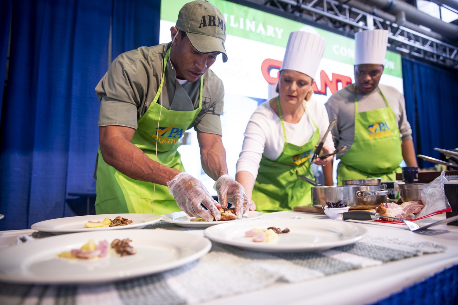 "<a href=""https://filesource.wostreaming.net/commonwealthofpa/photo/17651_AGRIC_ARMY_NAVY_COOKOFF_CZ_13.jpg"" target=""_blank"">⇣ Download Photo<br></a>Sergeant Pete O. Linton plates his dish with Sous Chefs Ali Lanyon and James Crumble of ABC27 News at the 2020 Army vs. Navy Cook-Off in Harrisburg on January 9, 2020."