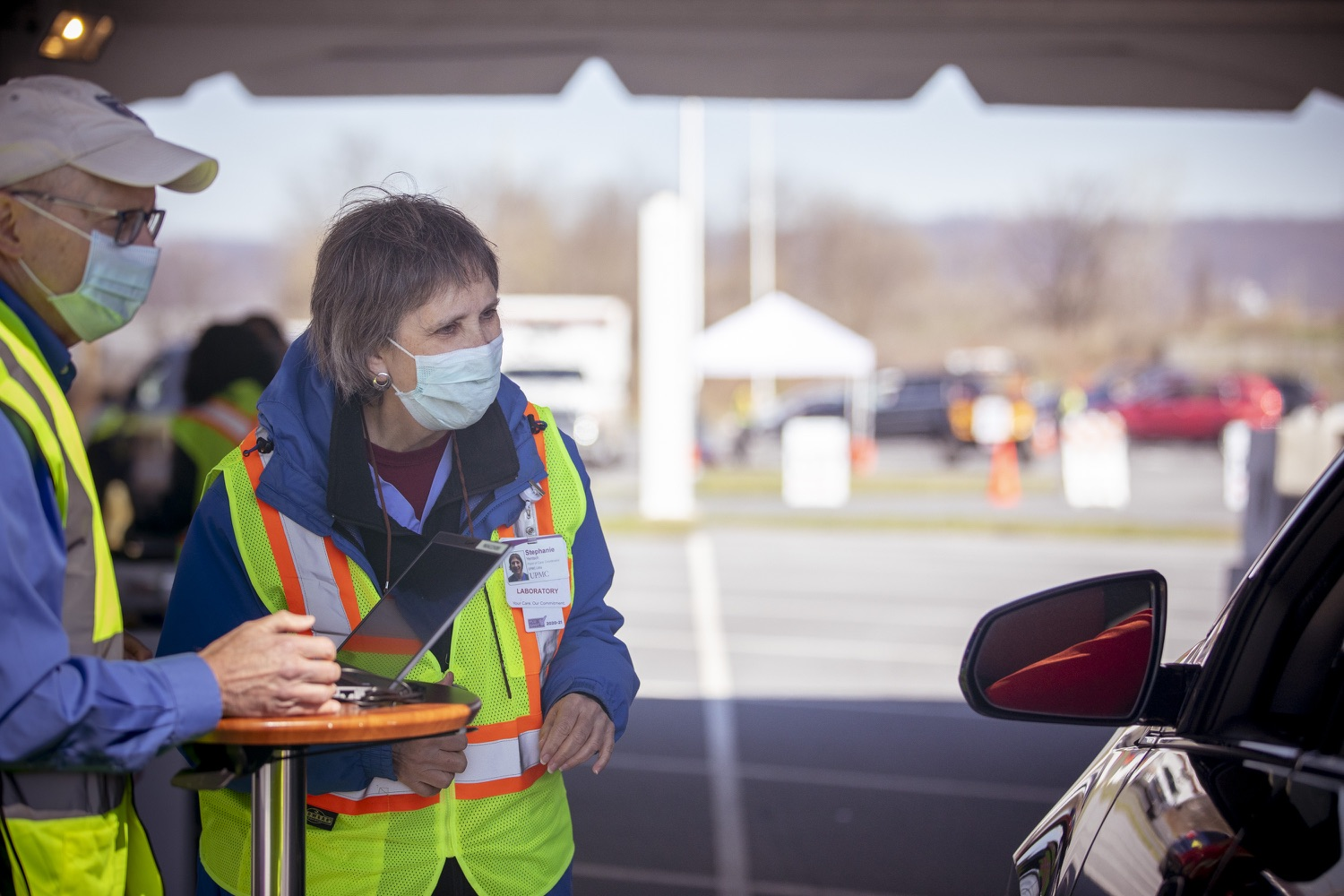 """<a href=""""https://filesource.wostreaming.net/commonwealthofpa/photo/18631_gov_hacc_vaccine_dz_019.jpg"""" target=""""_blank"""">⇣Download Photo<br></a>Workers at the vaccination site speaking with a driver.  Governor Wolf today visited the COVID-19 drive-thru mass vaccination clinic for Dauphin County residents at Harrisburg Area Community College. The drive-thru clinic was developed in partnership with UPMC Pinnacle and Dauphin County. He was joined by UPMC Pinnacle President Phil Guarneschelli and Dauphin County Commissioners Mike Pries and George P. Hartwick III.  HARRISBURG, PA -- March 30, 2021"""