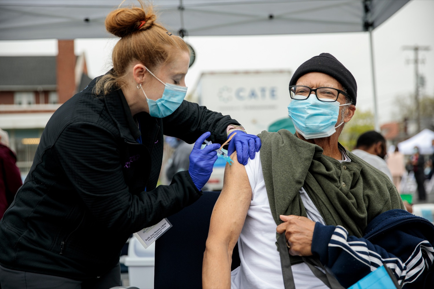 """<a href=""""https://filesource.wostreaming.net/commonwealthofpa/photo/18675_DOH_Beacon_Clinic_NK_002.jpg"""" target=""""_blank"""">⇣Download Photo<br></a>Beacon Clinic CRNP Kelli Ann Moore administers a Johnson and Johnson vaccine to Harrisburg resident Thermon E. Spence Sr., prior to a press conference, which discussed an upcoming COVID-19 mobile response vaccination tour to provide vaccinations and education to minority and underserved communities across the commonwealth, outside of Beacon Clinic in Harrisburg on Monday, April 12, 2021."""