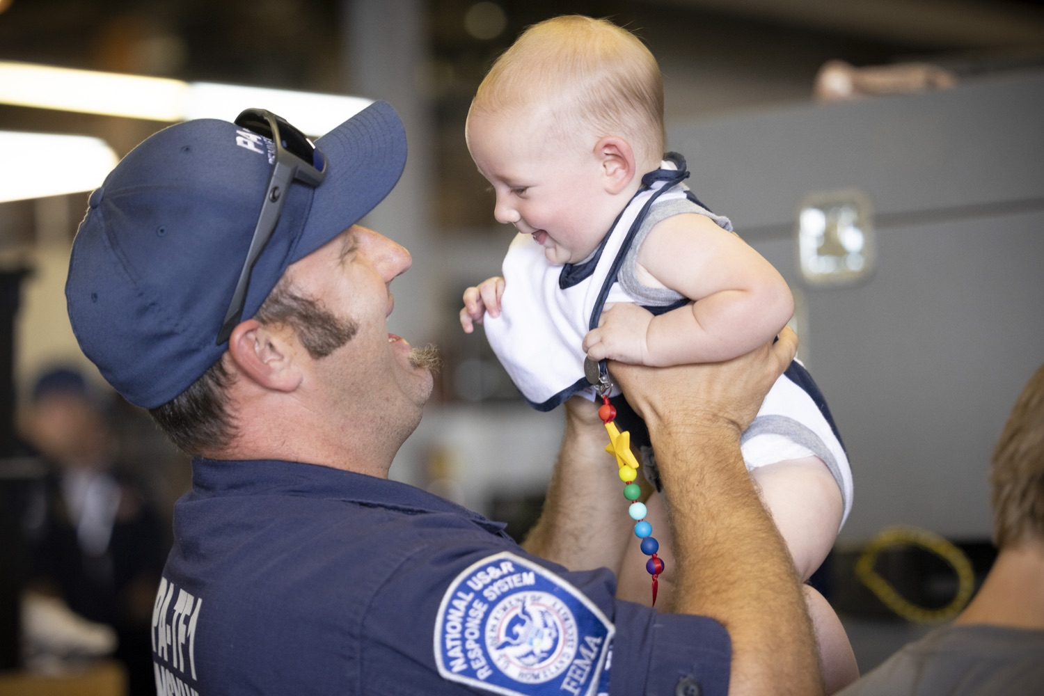 """<a href=""""https://filesource.wostreaming.net/commonwealthofpa/photo/18936_gov_taskforceone_dz_001.jpg"""" target=""""_blank"""">⇣Download Photo<br></a>Pennsylvania-Task Force 1 member James Obrien greeting his son Murphy.  Governor Tom Wolf thanked members of Pennsylvania-Task Force 1 (PA- TF1), who returned today to Philadelphia after spending two weeks assisting with search and rescue efforts at the site of the recent deadly building collapse in Surfside, Florida.  Philadelphia, Pa.  July 16, 2021"""