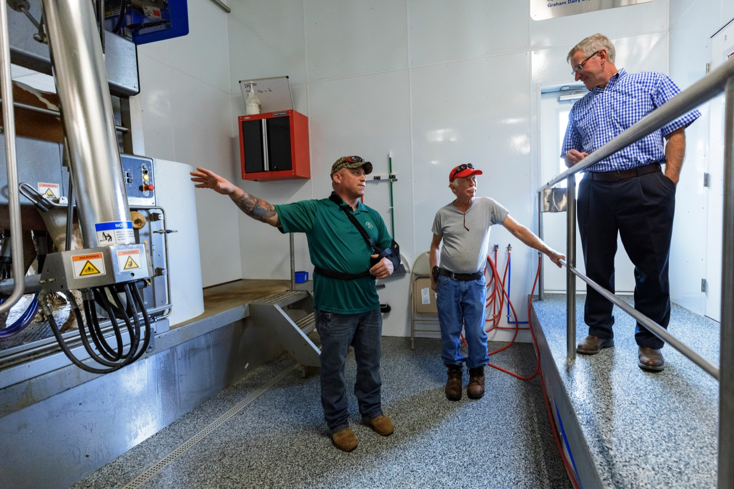 """<a href=""""https://filesource.wostreaming.net/commonwealthofpa/photo/19097_AG_DairyInnovation_NK_003.jpg"""" target=""""_blank"""">⇣Download Photo<br></a>PA Dept. of Agriculture Secretary Russell Redding gets a tour of the """"Robot Room"""" from Pleasant Lane Farms Todd Frye, co-owner, left, and father Ralph Frye, founder, center, at the farm in Latrobe on Thursday, September 9, 2021. In 2019, Pleasant Lane Farms reconstructed their operation and on-farm business plan to safeguard the farms future for the next generation. The Frye family constructed a new barn equipped with a robotic milker, atmospheric climate control to regulate barn temperature and cow brushes to promote cow comfort. The barn directly supplies the on-farm cheese processing facility, which received a $364,082 Pennsylvania Dairy Investment Program grant to support marketing and value-added processing equipment investments. Today, the creamery at Pleasant Lane Farms processes 15,000 to 25,000 pounds of milk and produces more 1,700 to 2,900 pounds of cheese each week."""