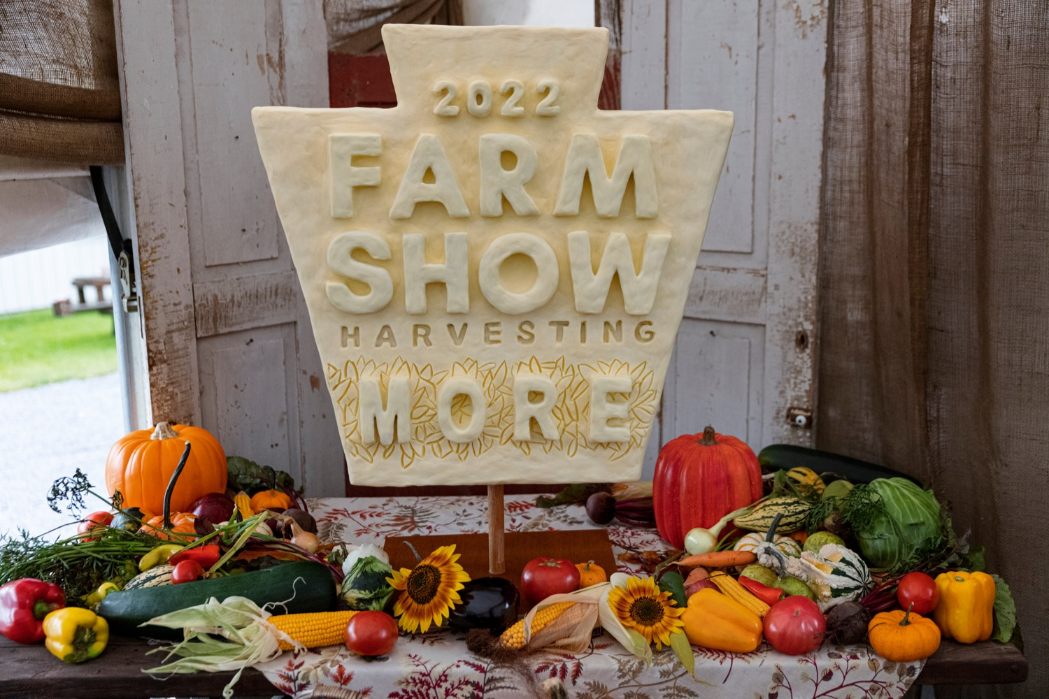 """<a href=""""https://filesource.wostreaming.net/commonwealthofpa/photo/19118_AG_FarmShowTheme_NK_001.jpg"""" target=""""_blank"""">⇣Download Photo<br></a>A 20-pound mini butter sculpture of the 2022 Harvesting More logo, sculpted by PA Garret McCall, winner of the 2021 Butter Up! competition held during the virtual 2021 PA Farm Show, is pictured at Vale Wood Farms in Loretto on Thursday, September 16, 2021."""