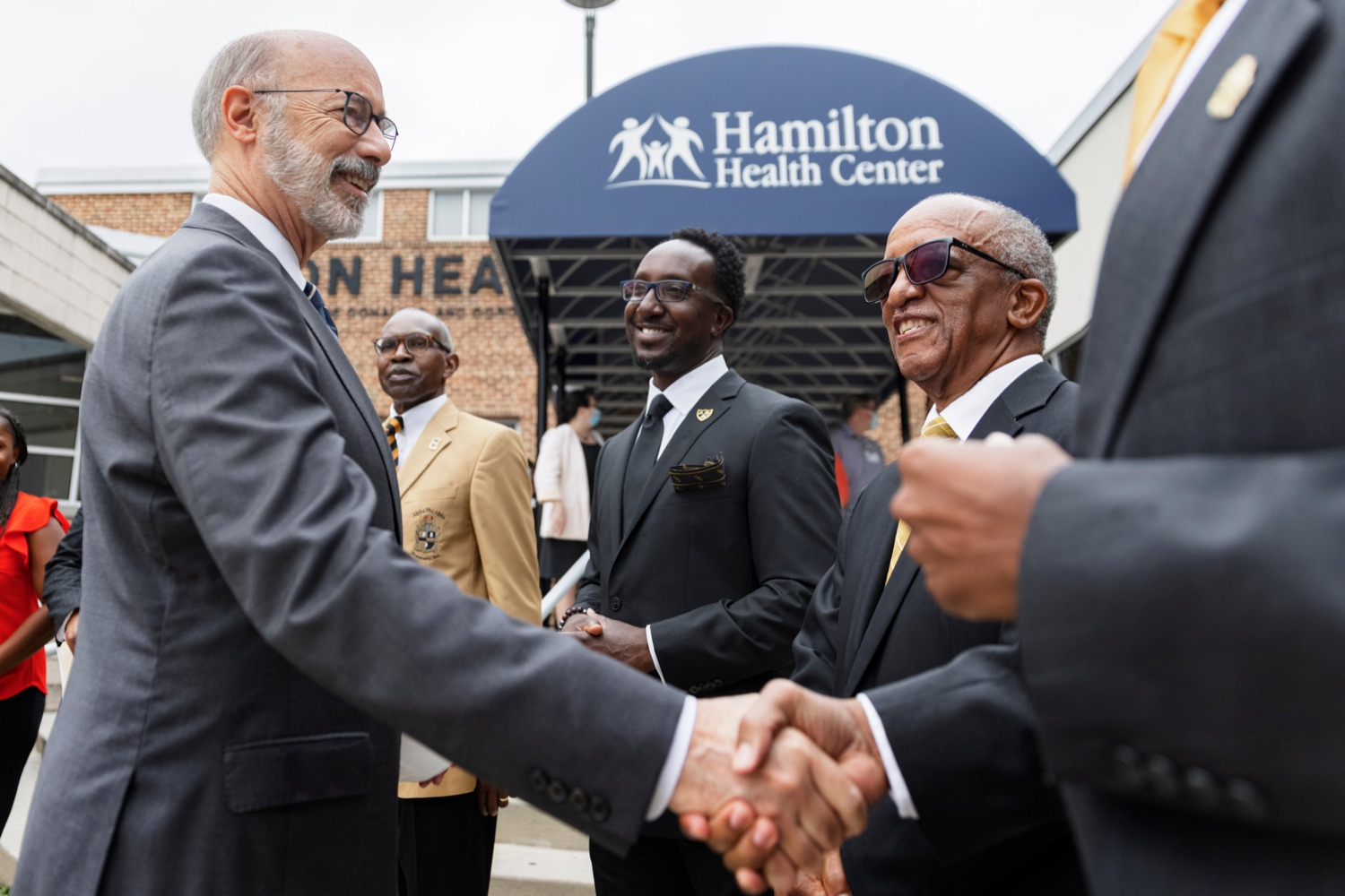 """<a href=""""https://filesource.wostreaming.net/commonwealthofpa/photo/20119_GOV_Vaccines_NK_008.jpg"""" target=""""_blank"""">⇣Download Photo<br></a>Governor Tom Wolf shakes hands with members of Zeta Theta Lambda Chapter of Alpha Phi Alpha fraternity, from left; Kenneth L Mickens, Dr. Cedric Harris, and Freddie Player, during a press conference, which encouraged eligible Pennsylvanians who are not yet vaccinated to take advantage of their upcoming community COVID-19 vaccine clinic in partnership with the Zeta Theta Lambda Chapter of Alpha Phi Alpha fraternity, outside Hamilton Health Center in Harrisburg on Wednesday, October 6, 2021. The clinic will run on Saturday, October 9, COVID-19 vaccinations will be offered from 10am  2pm at Hamilton Health Center, 100 S. 17th St., Harrisburg, PA 17104."""