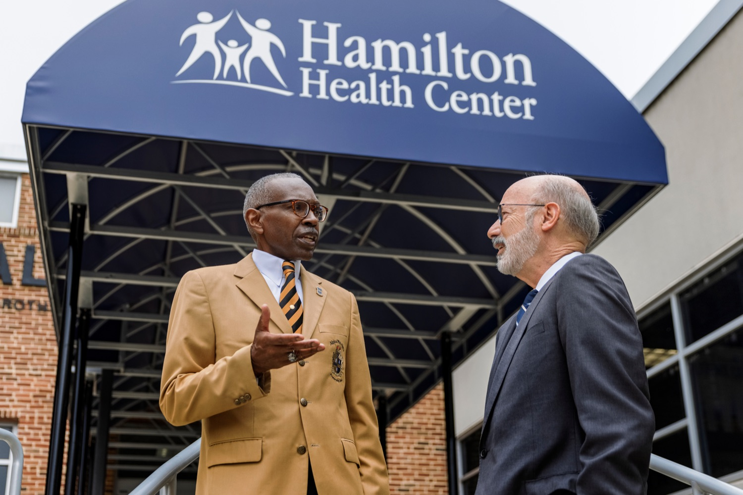 """<a href=""""https://filesource.wostreaming.net/commonwealthofpa/photo/20119_GOV_Vaccines_NK_015.jpg"""" target=""""_blank"""">⇣Download Photo<br></a>Governor Tom Wolf talks with Zeta Theta Lambda Chapter of Alpha Phi Alpha fraternity member Kenneth L. Mickens during a press conference, which encouraged eligible Pennsylvanians who are not yet vaccinated to take advantage of their upcoming community COVID-19 vaccine clinic in partnership with the Zeta Theta Lambda Chapter of Alpha Phi Alpha fraternity, outside Hamilton Health Center in Harrisburg on Wednesday, October 6, 2021. The clinic will run on Saturday, October 9, COVID-19 vaccinations will be offered from 10am  2pm at Hamilton Health Center, 100 S. 17th St., Harrisburg, PA 17104."""